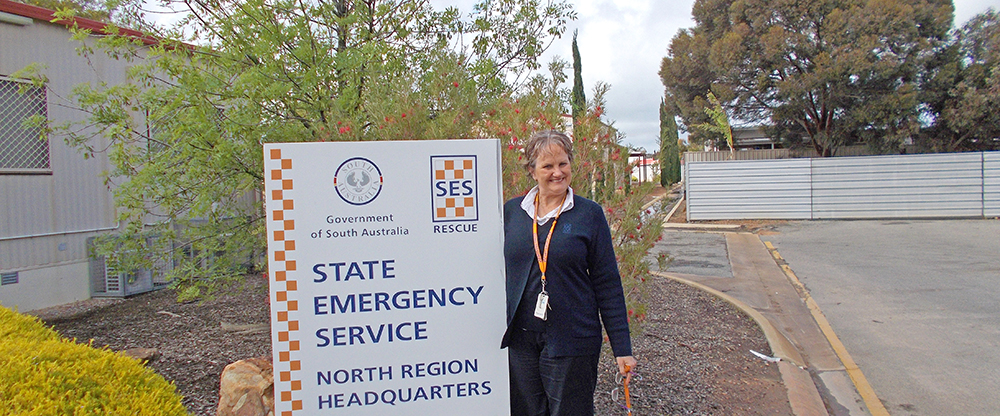 Sign outside the SA State Emergency Service North Region headquarters with an SES staff member standing beside it