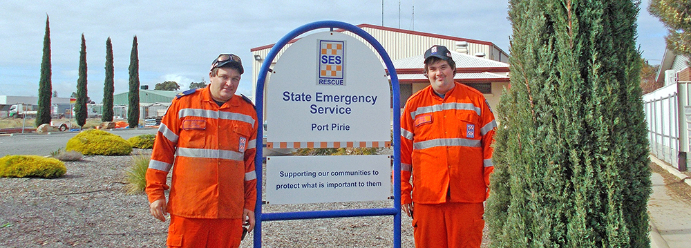 SA State Emergency Service volunteers standing beside a sign outside the Port Pirie Unit building