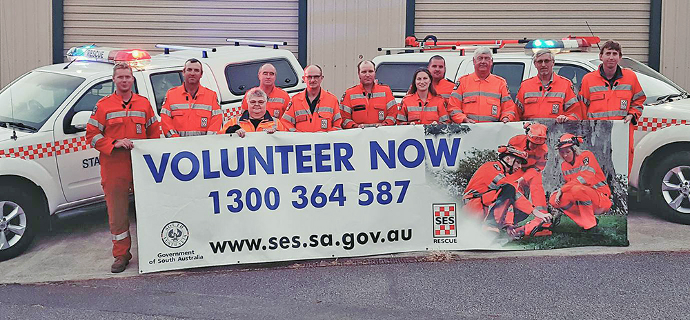 SA State Emergency Service Strathalbyn Unit volunteers standing in front of SES rescue vehicles holding a banner. Volunteer Now 1300 364 587